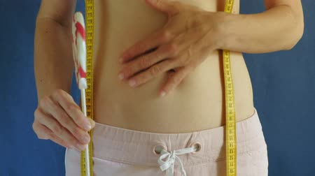 measure tape : woman with a flat belly. Close-up on a blue background. Healthy food, fitness