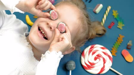 white out : Cheerful little girl lies on a blue background with sweets. Closeup portrait Stock Footage