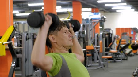 weightlifting : A man doing a bench press with dumbbells sitting with a straight grip in a fitness studio Stock Footage
