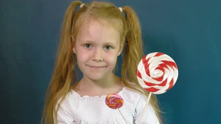 язык : Little girl with a lollipop on a blue background. Close up portrait