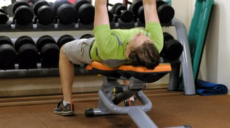 gewichtheffen : Man doing bench press with dumbbells in fitness studio