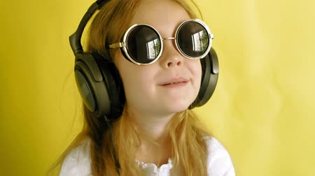 use computer : Cheerful little girl in headphones on a yellow background. Closeup portrait. Stock Footage