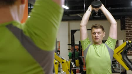 tense : Man doing bench press with dumbbells in fitness studio
