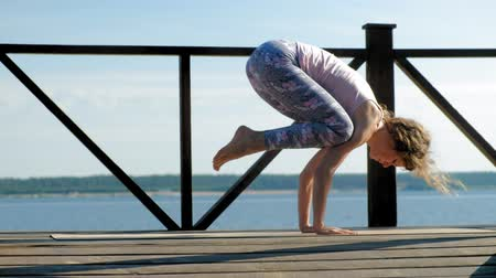 karga : Young woman practicing yoga outdoors in summer. Healthy lifestyle