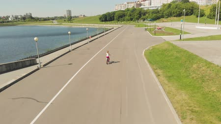 evez : Young woman riding a bicycle outdoors in summer. River embankment. Eco-friendly transport. Aerial shooting