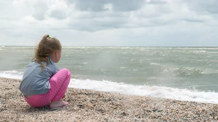 ракушки : Little girl on the sea beach collects shells. Summer Стоковые видеозаписи