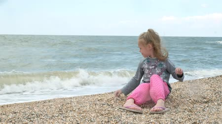 Little girl on the sea beach collects shells. Summer Stock mozgókép