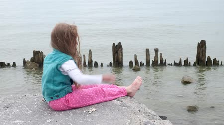 Girl child sitting on the stones on the seashore. Stock mozgókép