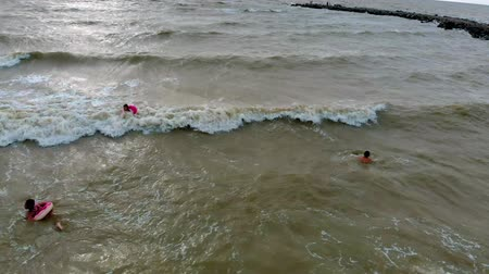 People in rubber rings swim on the waves in the sea. Aerial video Stock mozgókép