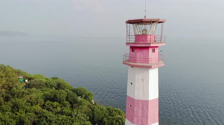 latarnia morska : Flying around the lighthouse on the seashore. Aerial shot