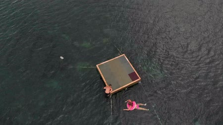 jangada : Cheerful children are jumping into the sea from a raft. Aerial shot