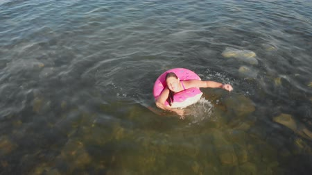 いかだ : A girl floats on a rubber ring in the sea. Sea vacations in summer. Aerial shot