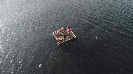 jangada : Cheerful teenagers are jumping into the sea. Aerial shot
