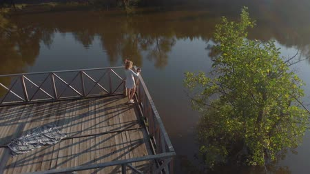 uses : A young woman uses a tablet by the river. Aerial shot Stock Footage