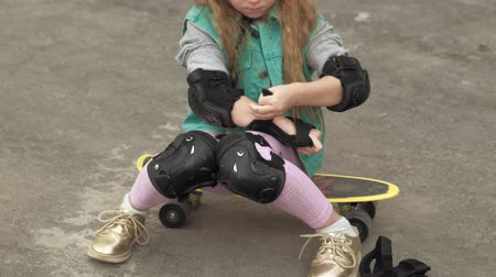 肘 : Little girl dresses protection: helmet, knee pads and elbow pads. Sunset 動画素材