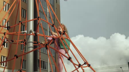 monkey : A child climbs a rope horizontal bar in an outdoor playground Stock Footage