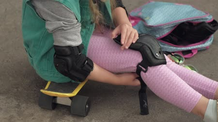 波打つ : Little girl dresses protection: helmet, knee pads and elbow pads. Sunset 動画素材