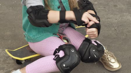 скейтборд : Little girl dresses protection: helmet, knee pads and elbow pads. Sunset Стоковые видеозаписи
