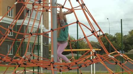 school children : A child climbs a rope horizontal bar in an outdoor playground Stock Footage