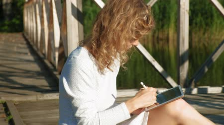 wooden bridge : Woman is using a computer tablet outdoors.