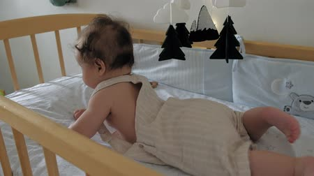 first person : Toddler girl learning to keep her head lying in a crib. Stock Footage