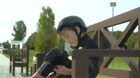 senta : A preschooler boy sits on a bench in the park and puts protection on his head, knees and arms. Summer
