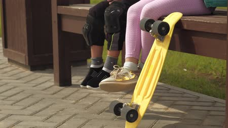 their : Children are sitting on a bench, moving their legs, a yellow skateboard is standing next to it. Stock Footage