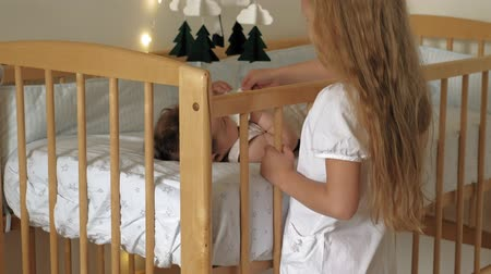 guardian : Girl preschool girl stands at the crib with a child, soothes her. Caring for a little sister