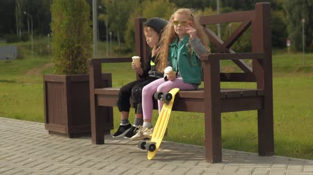 védősisak : A boy and a girl are sitting on a park bench and eating ice cream. Summer Stock mozgókép