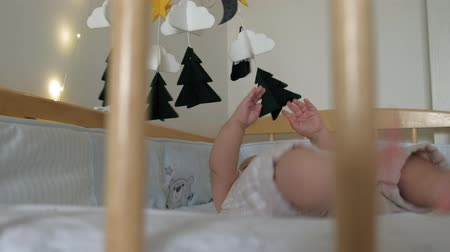 гелий : The kid plays with the mobile in the crib.