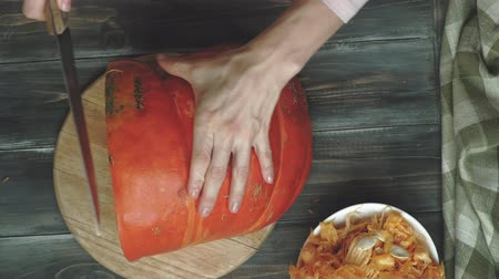 masa örtüsü : A man cuts an orange pumpkin.