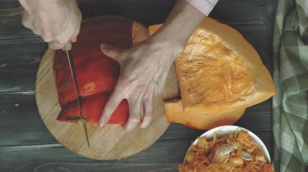 toalha de mesa : A man cuts an orange pumpkin.