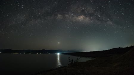 dişli doruk : 4K Timelapse day to night , the Milky Way and faded away when the sun rises. At Khlong Din Daeng Reservoir.