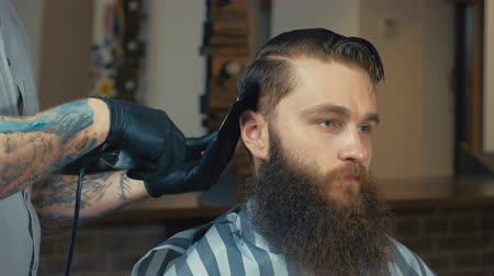vágás : Unparalleled barber with a beard and a tattoo is cutting the hair of his client in the barbershop. He is using a cutting comb and a hair clipper. Stock mozgókép