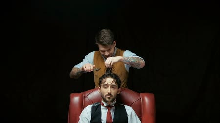 barbering : Barber cuts client with scissors hair. On a black background.