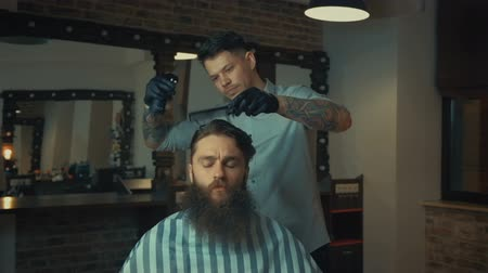 kuaför : Young handsome barber making haircut of attractive bearded man in barbershop Stok Video