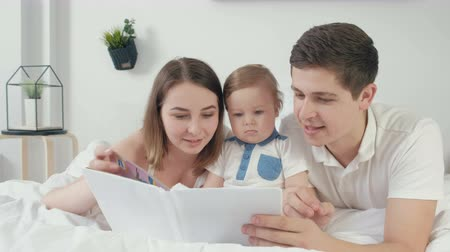 ded : happy loving family. pretty young mother and ded reading a book to her daughters Stock Footage
