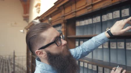 ustawa : Handsome well-dressed man stands by bookshelves in a room with classic interior. Man with a long beard. Wideo