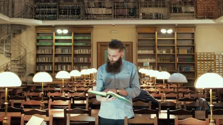 bookshop : male student with open book working in a library Stock Footage