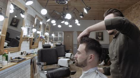 erkek güzellik : Handsome bearded man is smiling while having his hair cut by hairdresser at the barbershop