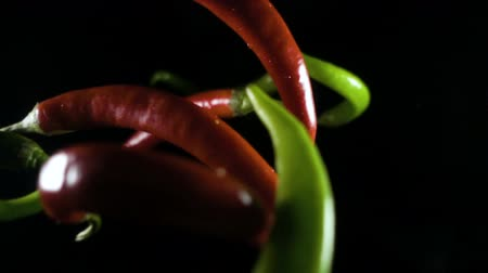 chili : Red and green chili peppers on black background