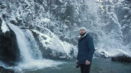 icefall : Photographer takes pictures of the frozen waterfall Periknik in the Ukrainian Carpathians