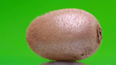 edények : Ripe juicy kiwi spinning on a green screen