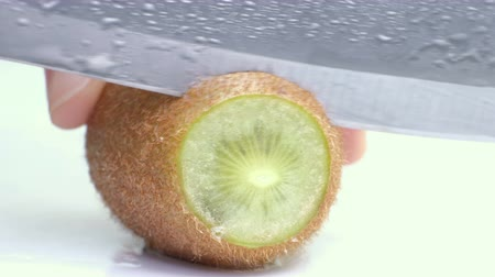doğrama : Kiwi being sliced in half on wet white background. Close up