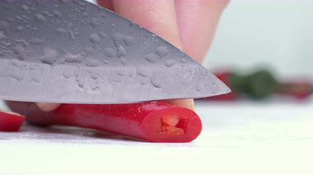 diferença : Red peppers on cutting board and knife on white background.