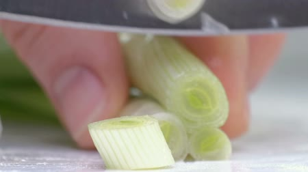 eat : Cut the green onions with a knife on the board. Cutting green without hands in the frame. Chef cuts the ingredients for soup. Close up