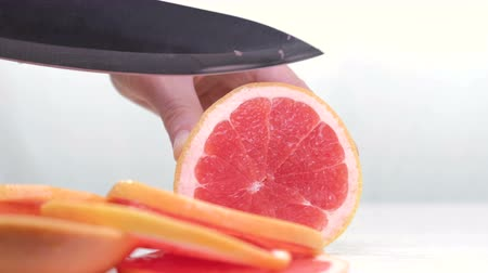 grejpfrut : Grapefruit fillets and half of a red grapefruit on a marble chopping board and white background 4K