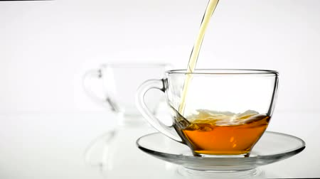 panelas : Black tea is poured into a glass beaker from a glass teapot. Slow motion. White background Stock Footage