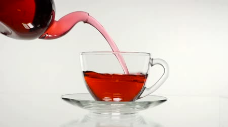 hibiscus tea : red rose tea in a glass teapot and a cup on a white background. Stock Footage