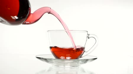 hibiscus : red rose tea in a glass teapot and a cup on a white background. Stock Footage